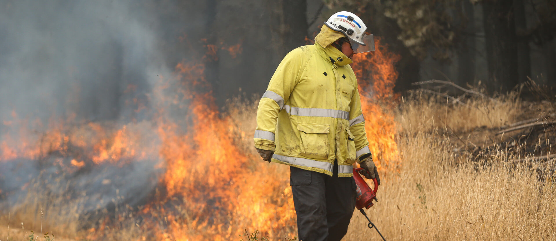 Firefighter creating firebreak with torch